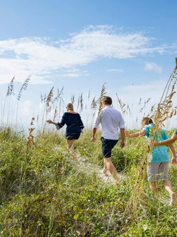 Family of four walk up grassy dunes toward the ocean