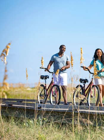man and woman walk next to bicycles along boardwalk