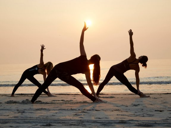 three women silhouetted against the sun, doing yoga on the beach