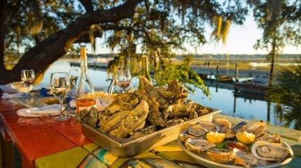 Oysters and champagne laid out on picnic table next to river