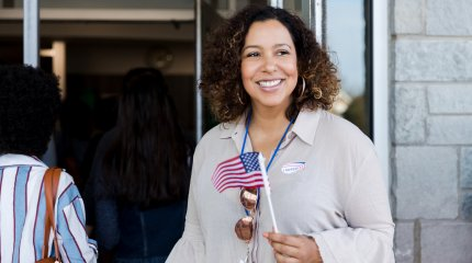 Woman smiles, holding American flag as she waits to vote